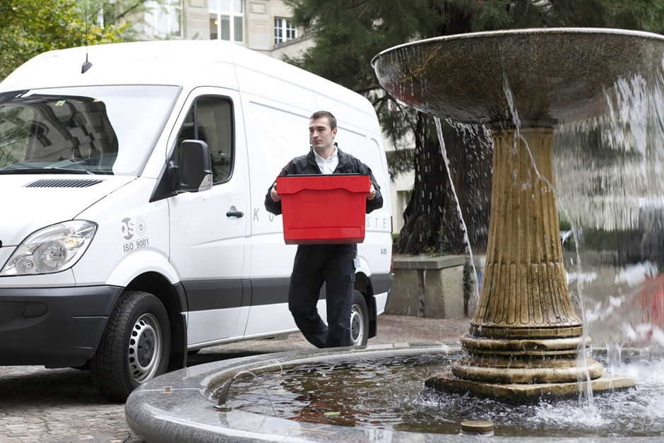 Delivery Van and driver carrying a red box walking behind a fountain