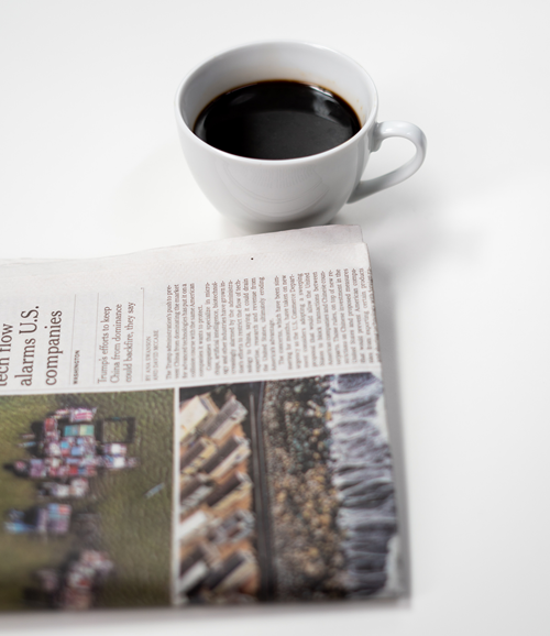 Cup of coffee with a newspaper on a white table